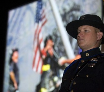Irvine Police officer Scott Larson stands at attention as part of the color guard during a 9/11 Commemoration Ceremony at Irvine Valley College on Tuesday. Images of the terror attacks were shown on a screen including this image of the flag raising at ground zero in the rubble of the twin towers.                                  ///ADDITIONAL INFO:                  03.iwn.memorial.0913.pb      Shot:  09/11/12         Paul Bersebach, The Orange County Register